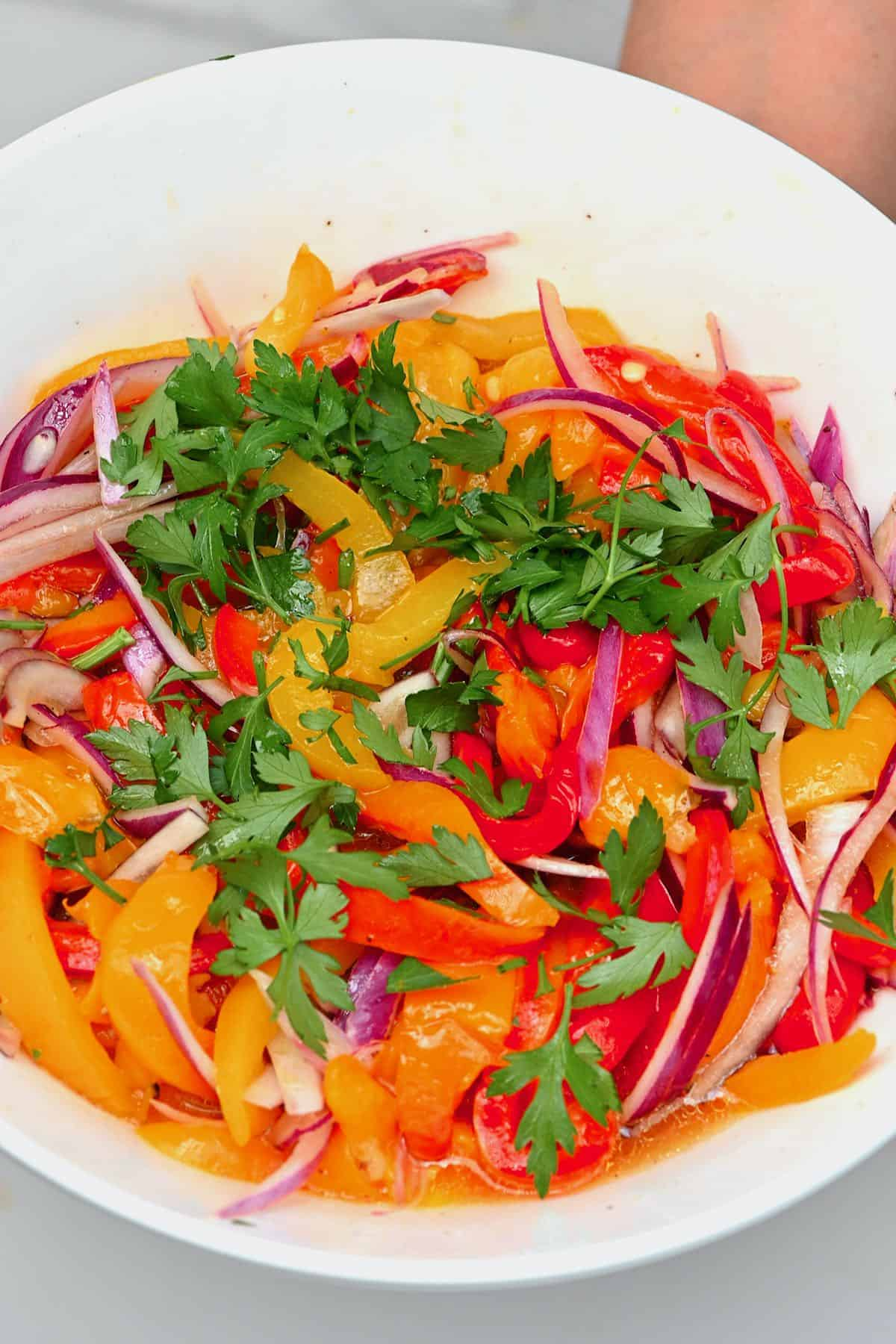 Roasted pepper salad topped with parsley in a bowl