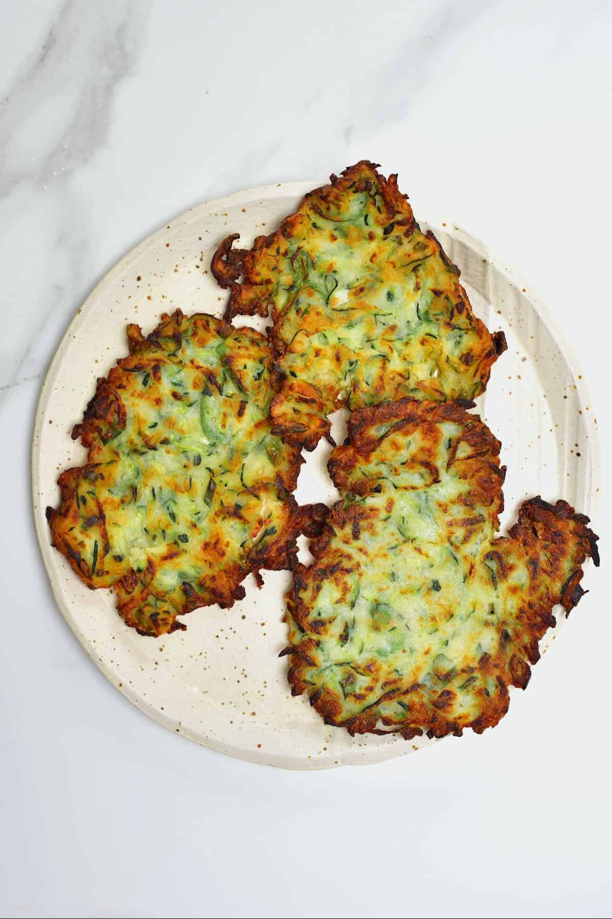 Three zucchini fritters in a plate
