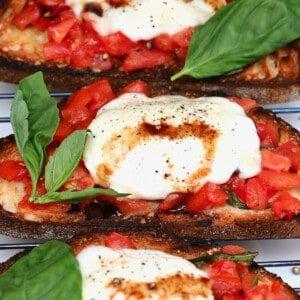 Mozzarella and tomato bruschetta with basil leaves