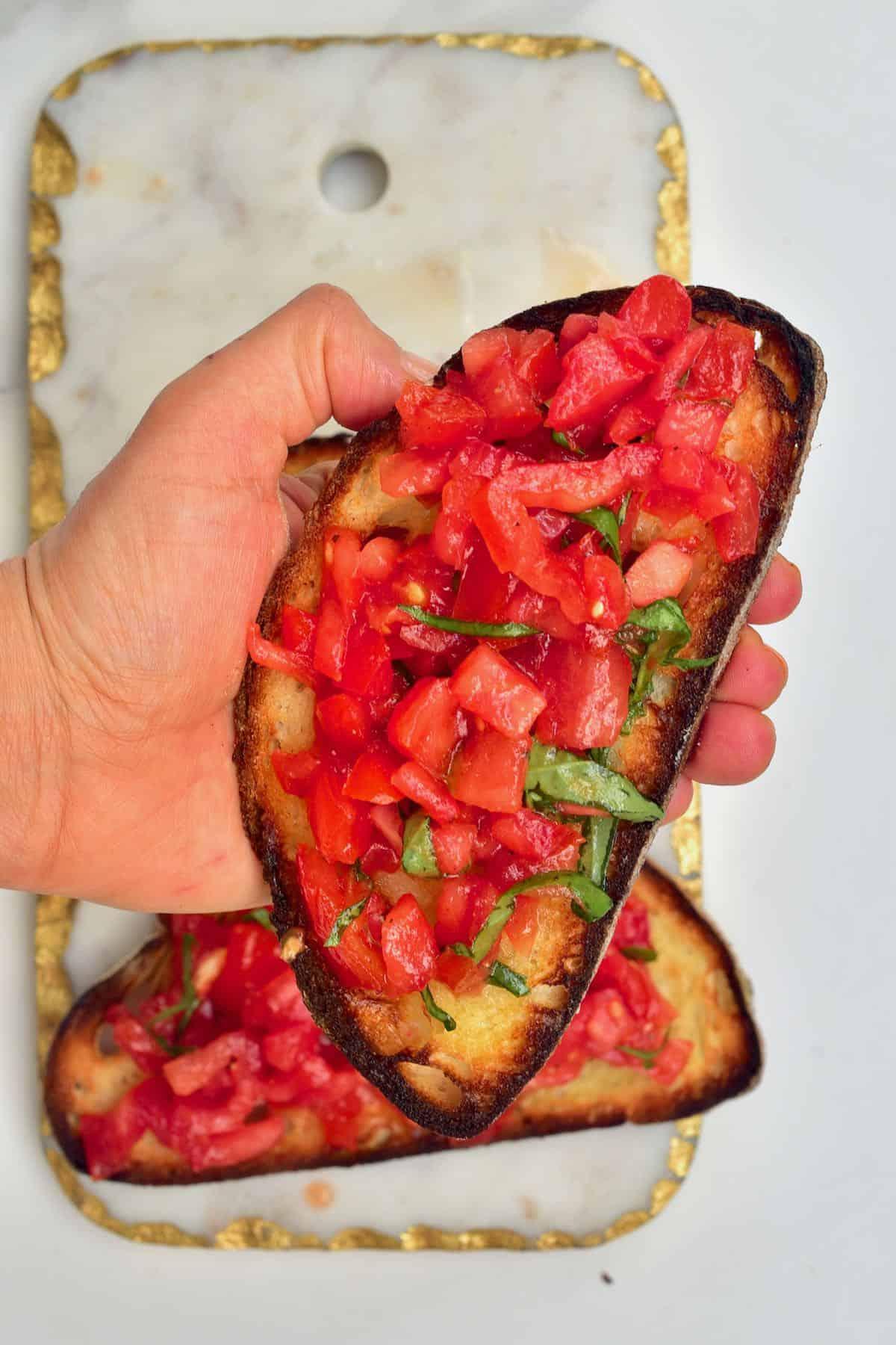 Hand holding a tomato bruschetta