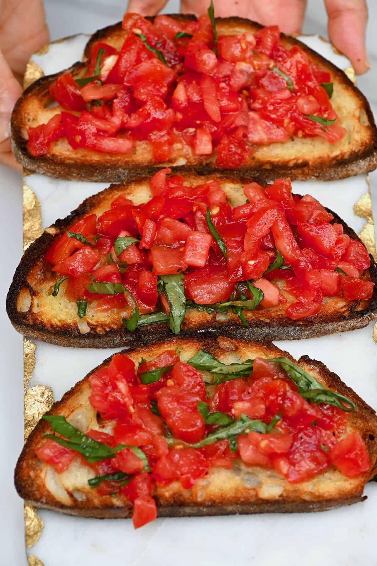 Three tomato bruschetta with basil