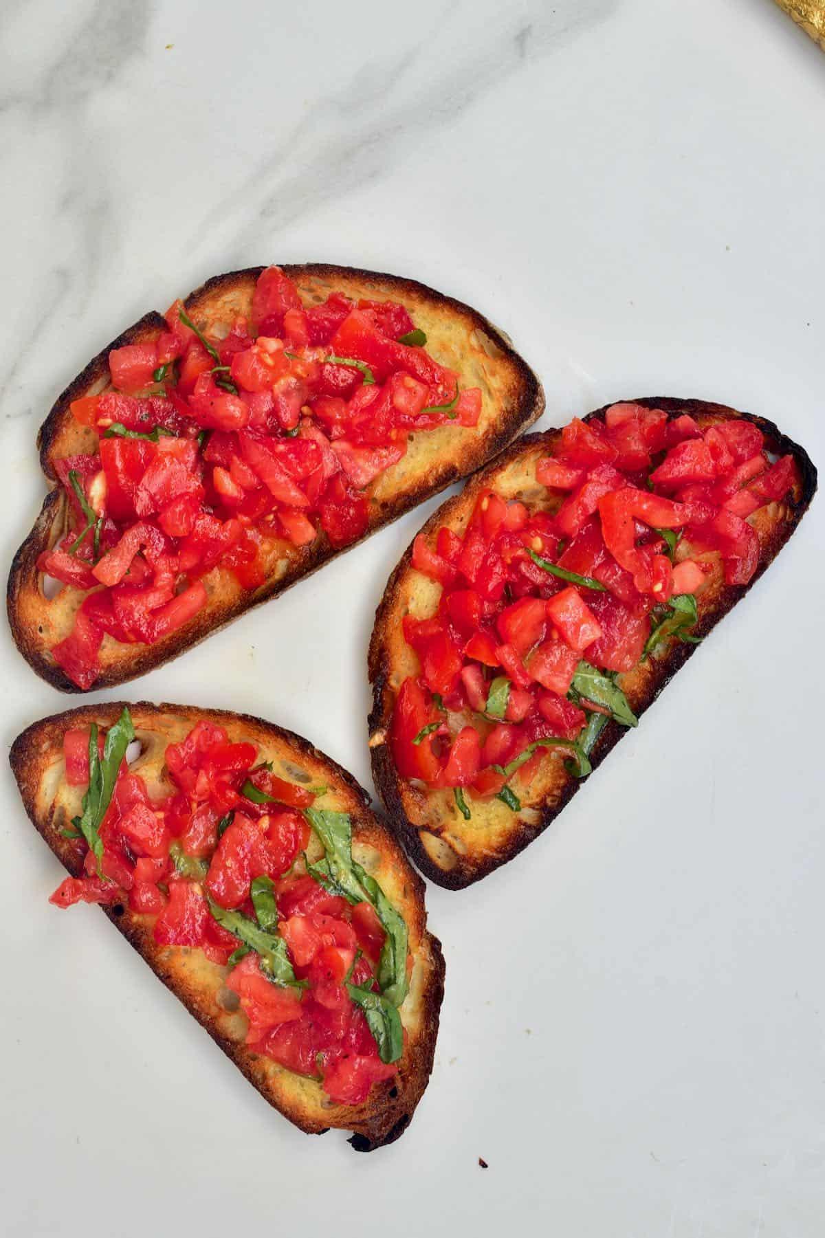 Three tomato bruschetta on flat surface