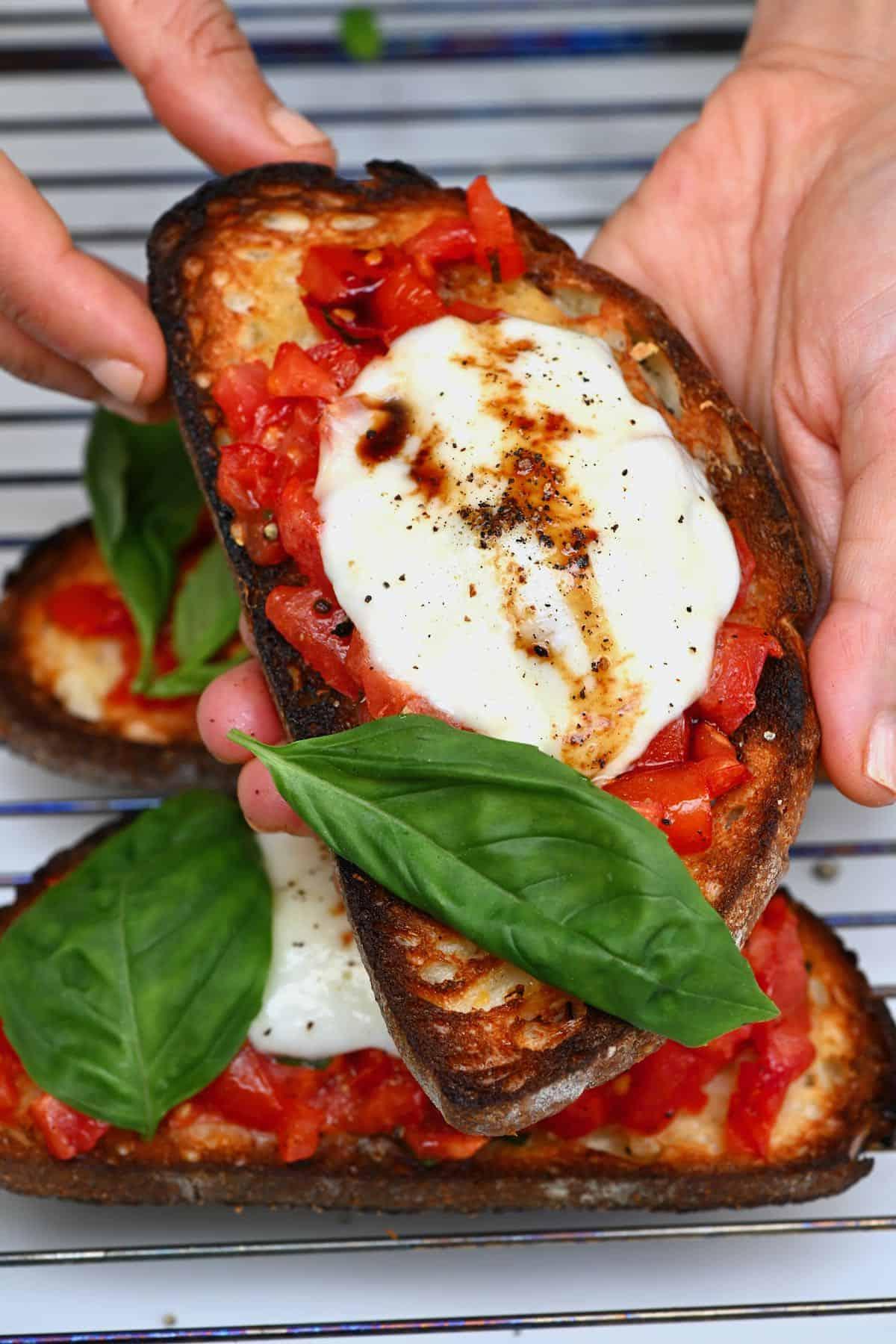 Hand holding a mozzarella bruschetta