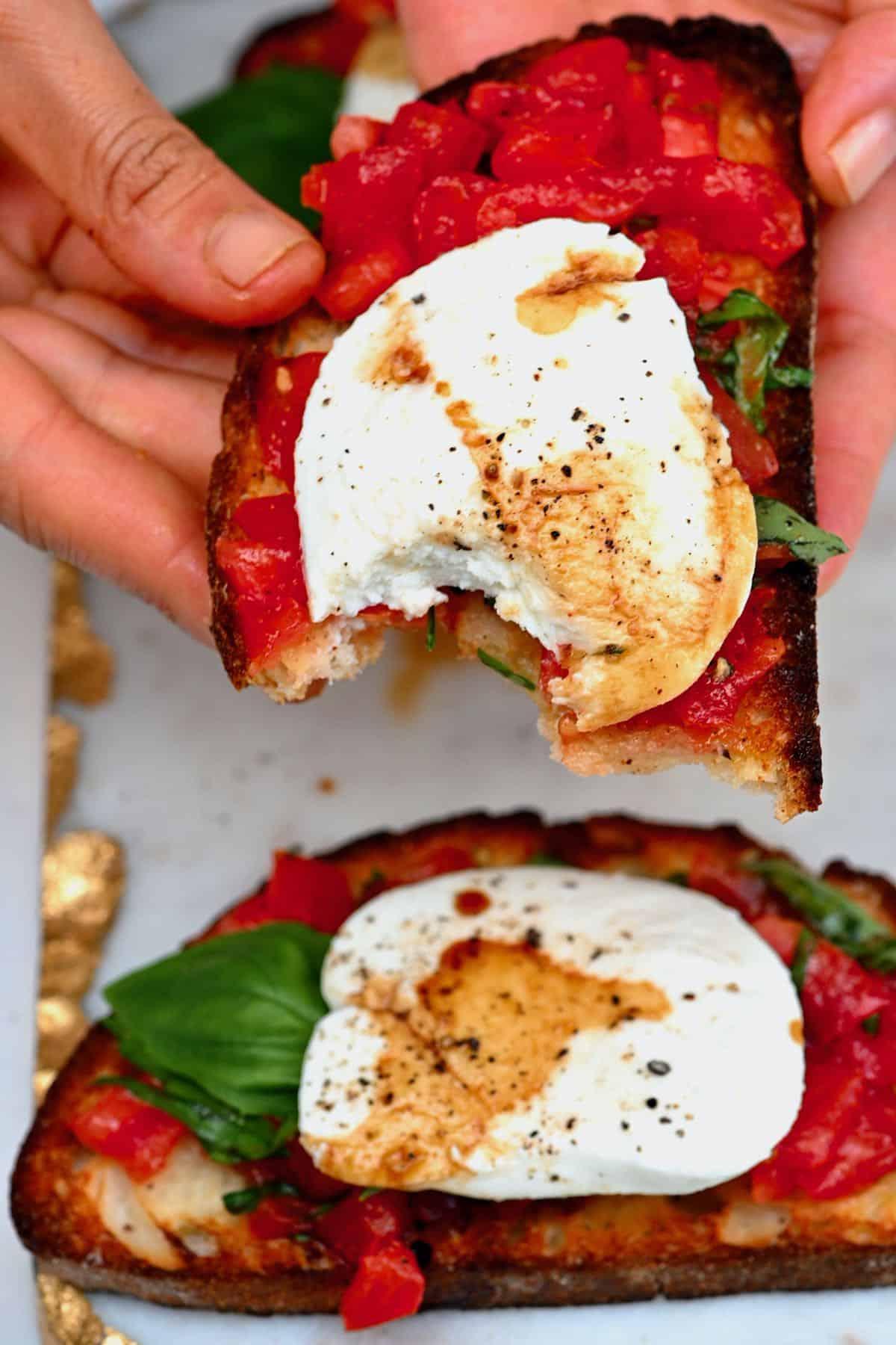Mozzarella bruschetta with a bitten off piece