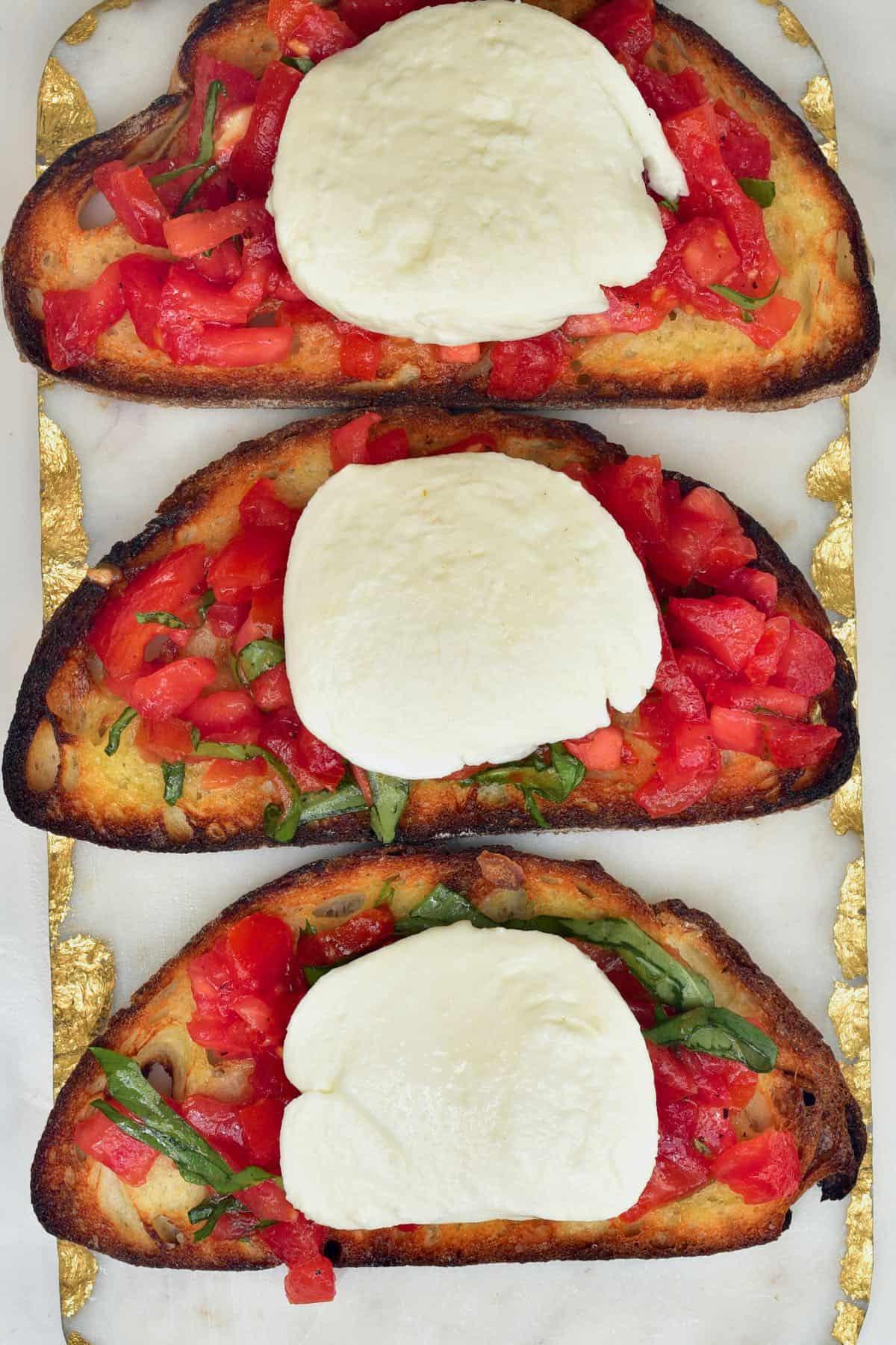 Three bruschettas with mozzarella