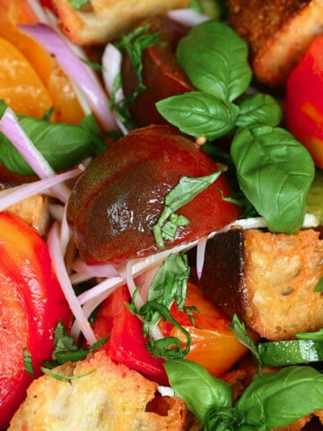Panzanella salad topped with basil leaves