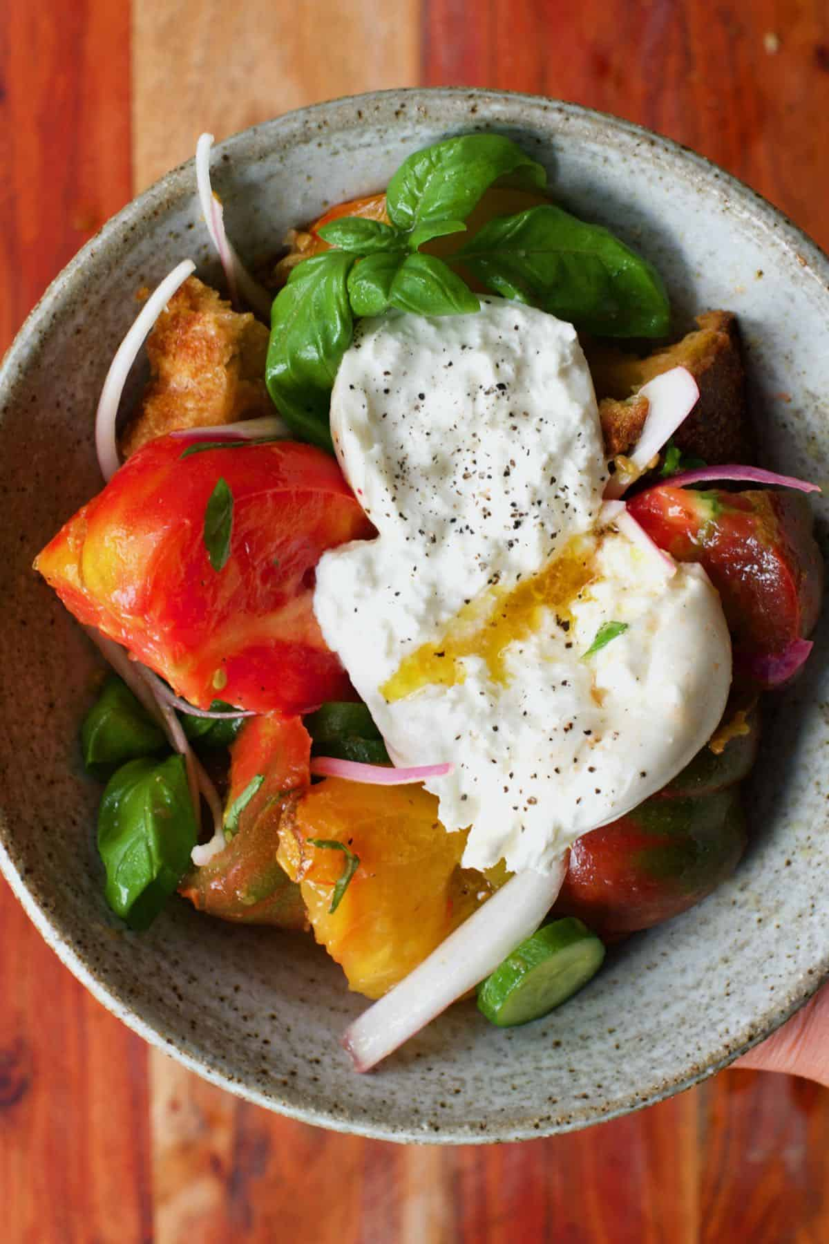 Panzanella salad topped with cheese
