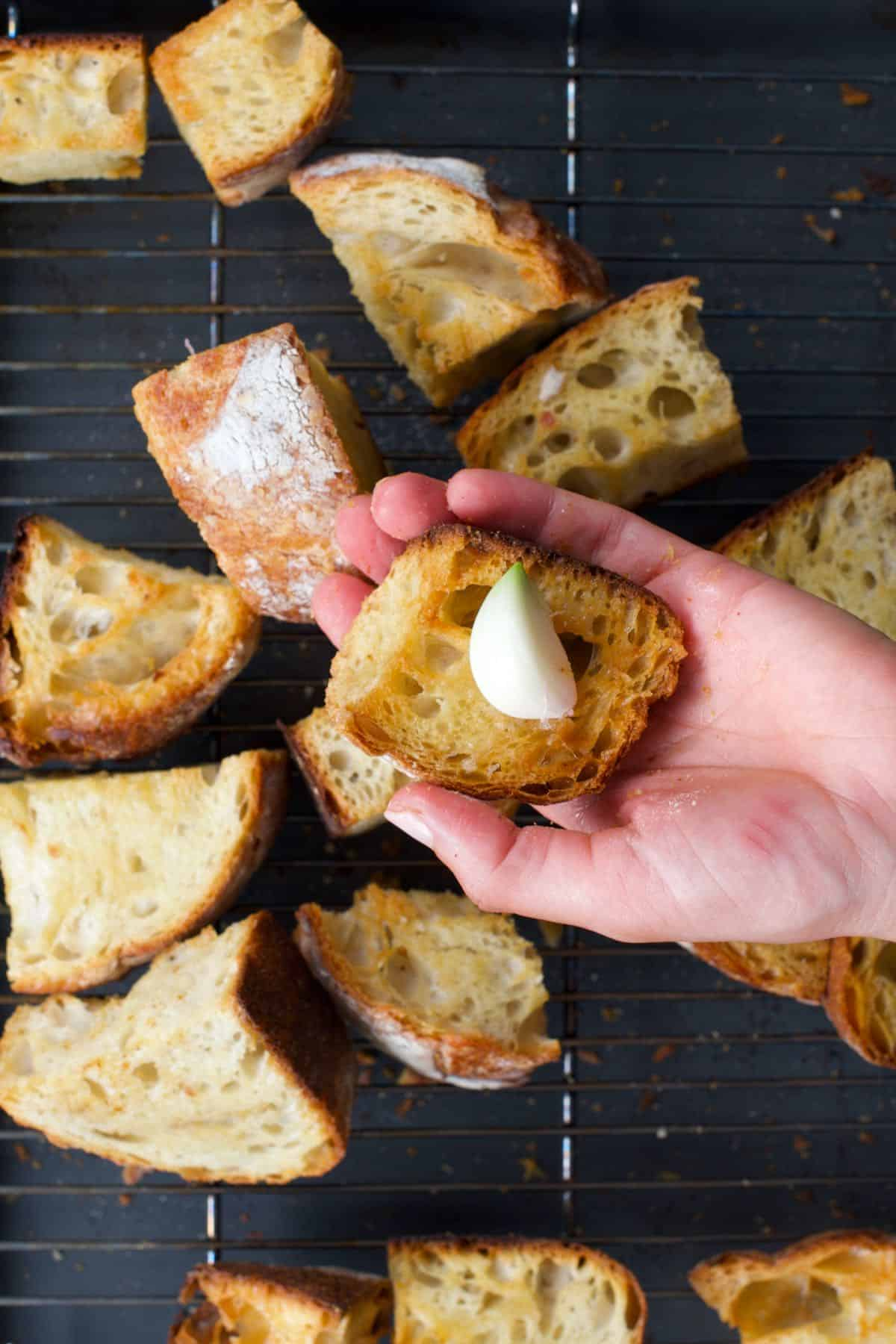 Rubbing garlic on roasted bread
