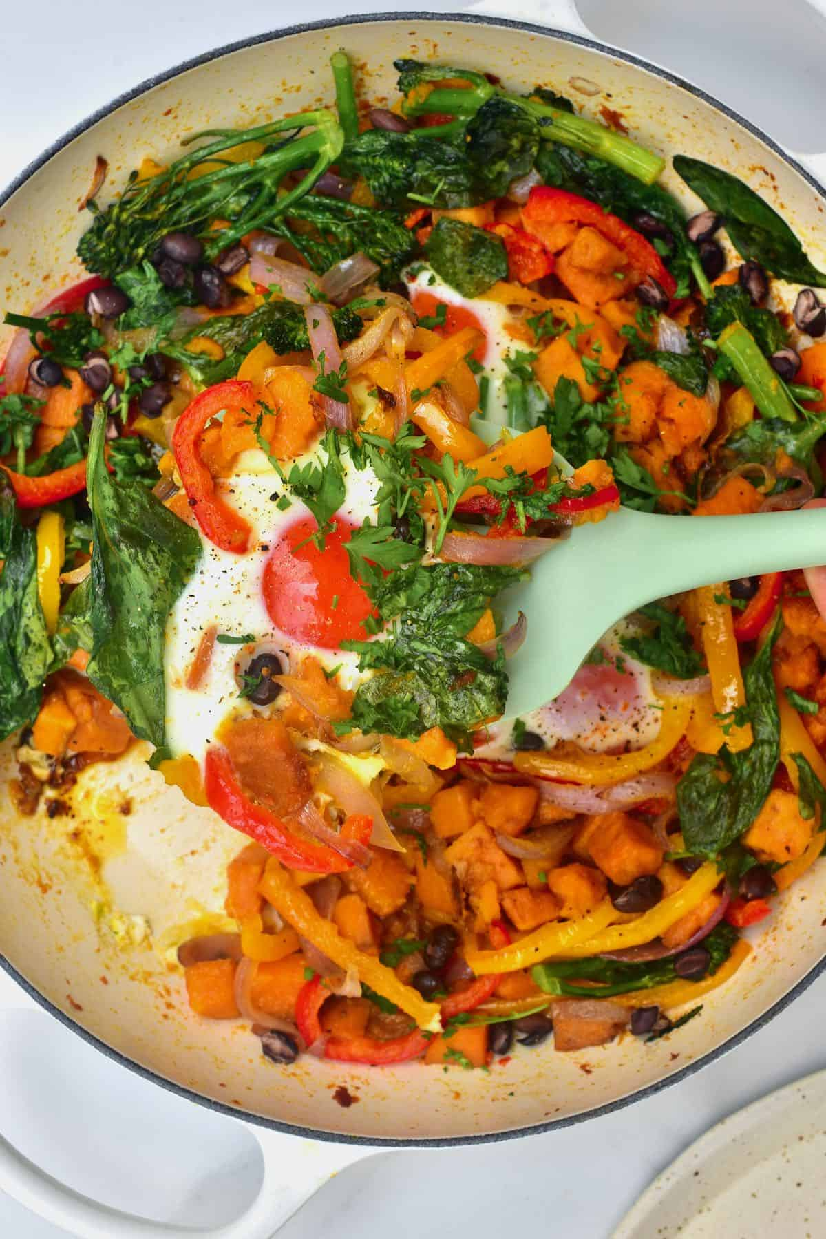 A pan with sweet potato hash and eggs