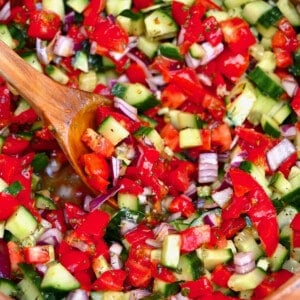 A spoonful of shirazi salad in a large bowl