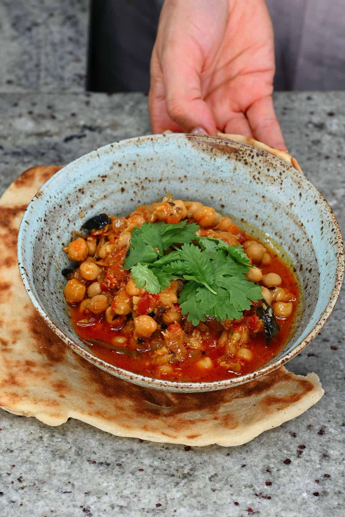 A bowl of chickpea curry and naan bread