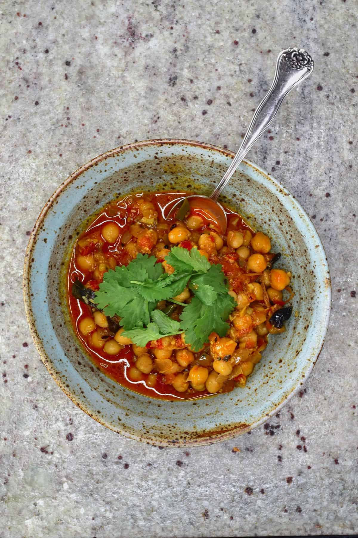 Chickpea curry in a bowl with a spoon