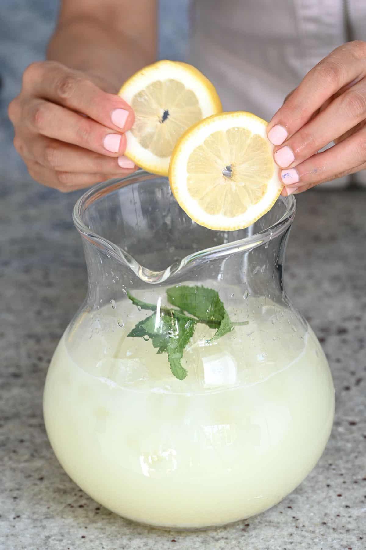 Adding lemon slices to creamy lemonade