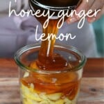 Pouring honey over a jar with lemon and ginger