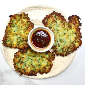 Three Korean Crispy Vegan Zucchini Fritters and dipping sauce on a plate