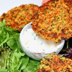 Vegetable fritters over yogurt sauce and salad