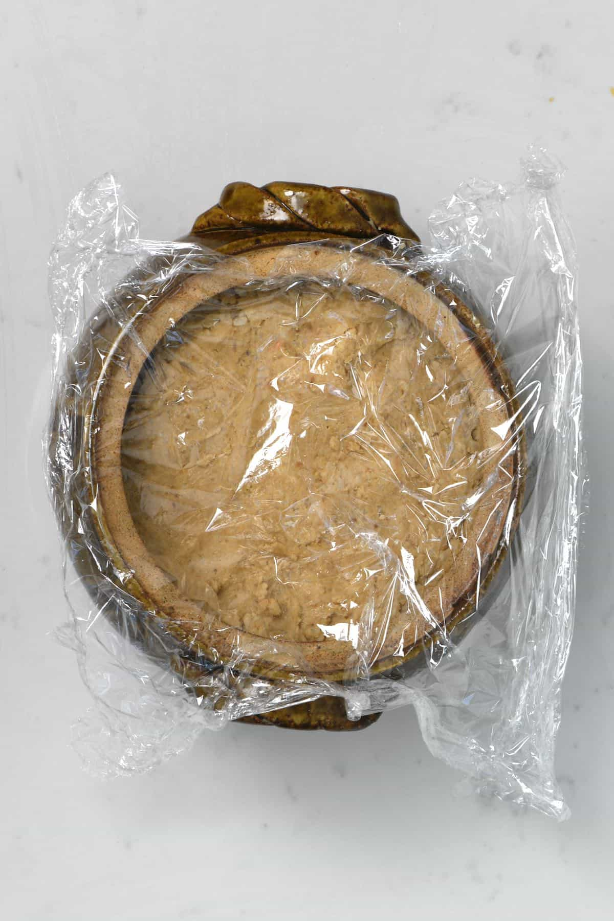 A container with miso paste covered with plastic wrap