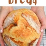 Hands holding no-knead bread loaf