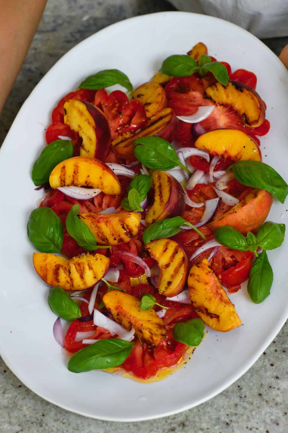 A plate with peach tomato salad