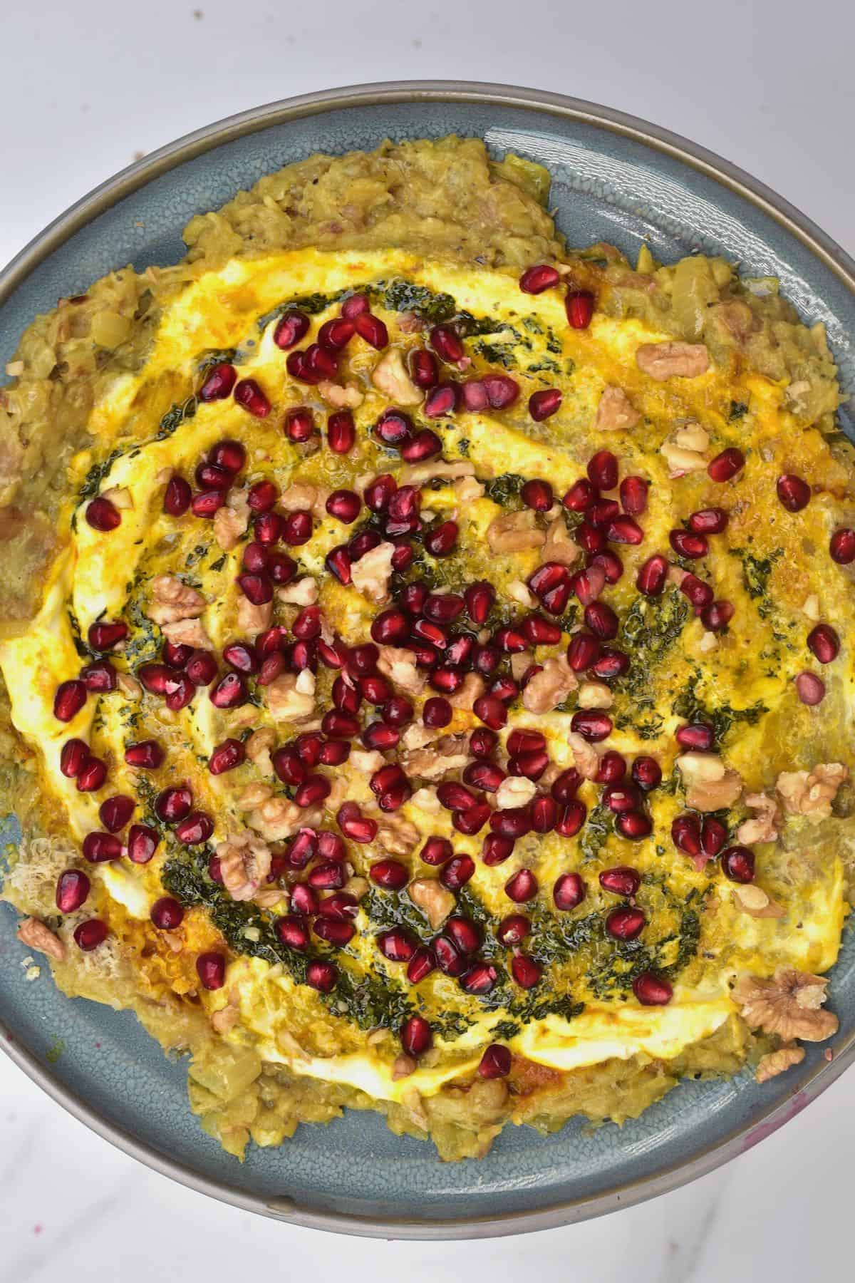 Kashke bademjan topped with pomegranate seeds