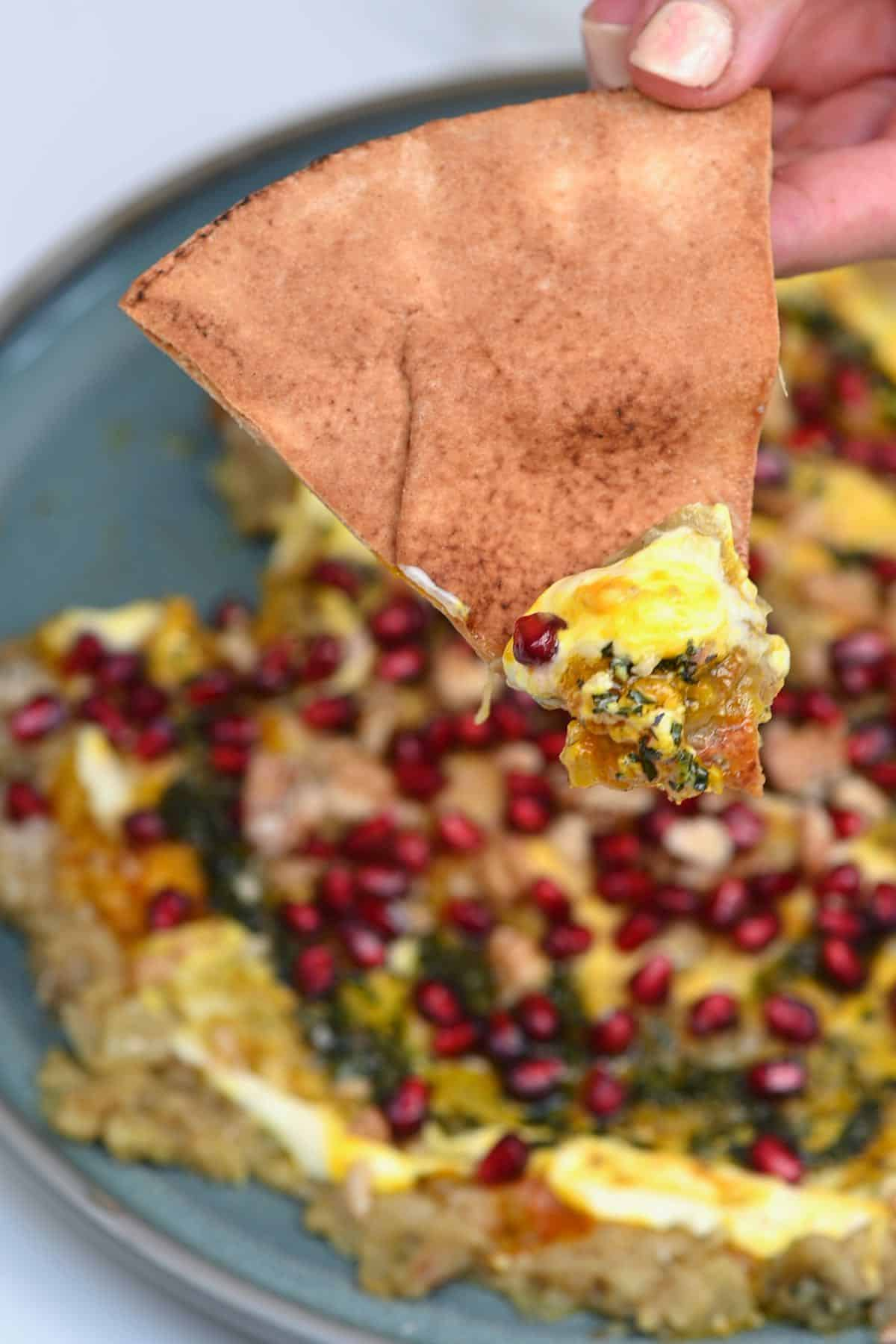 Scooping Kashke bademjan with pita bread