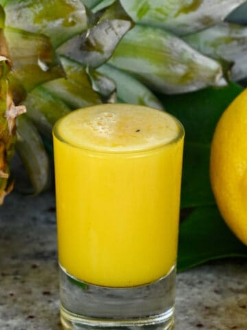 A shot glass with pineapple ginger juice