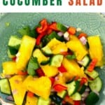 Pineapple cucumber salad in a bowl with a fork