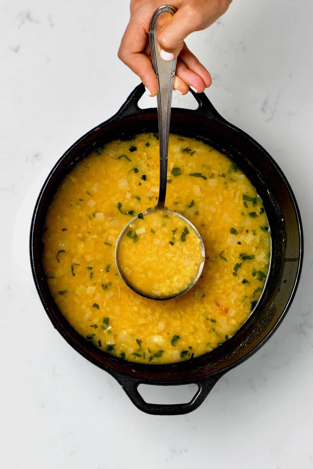 A ladle with lentil soup over a pan