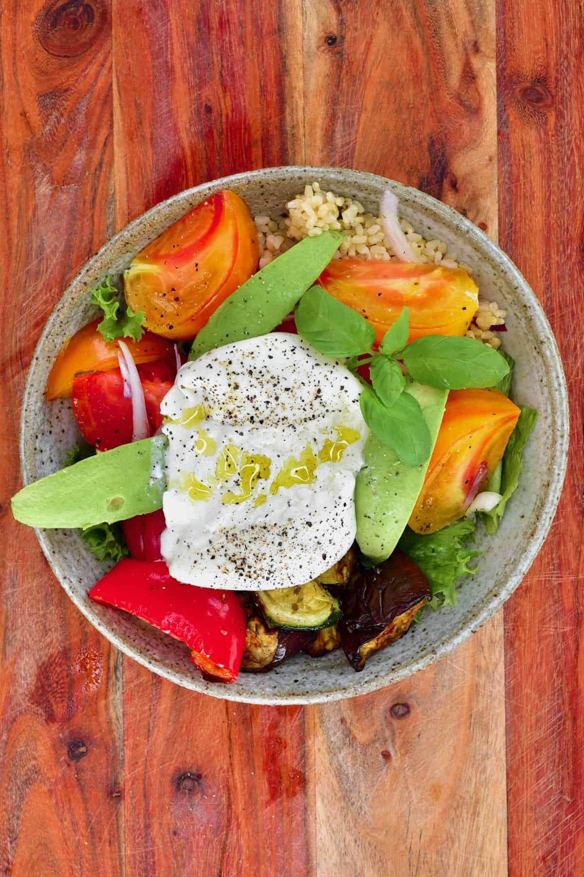 A bowl with roasted veggie salad and burrata