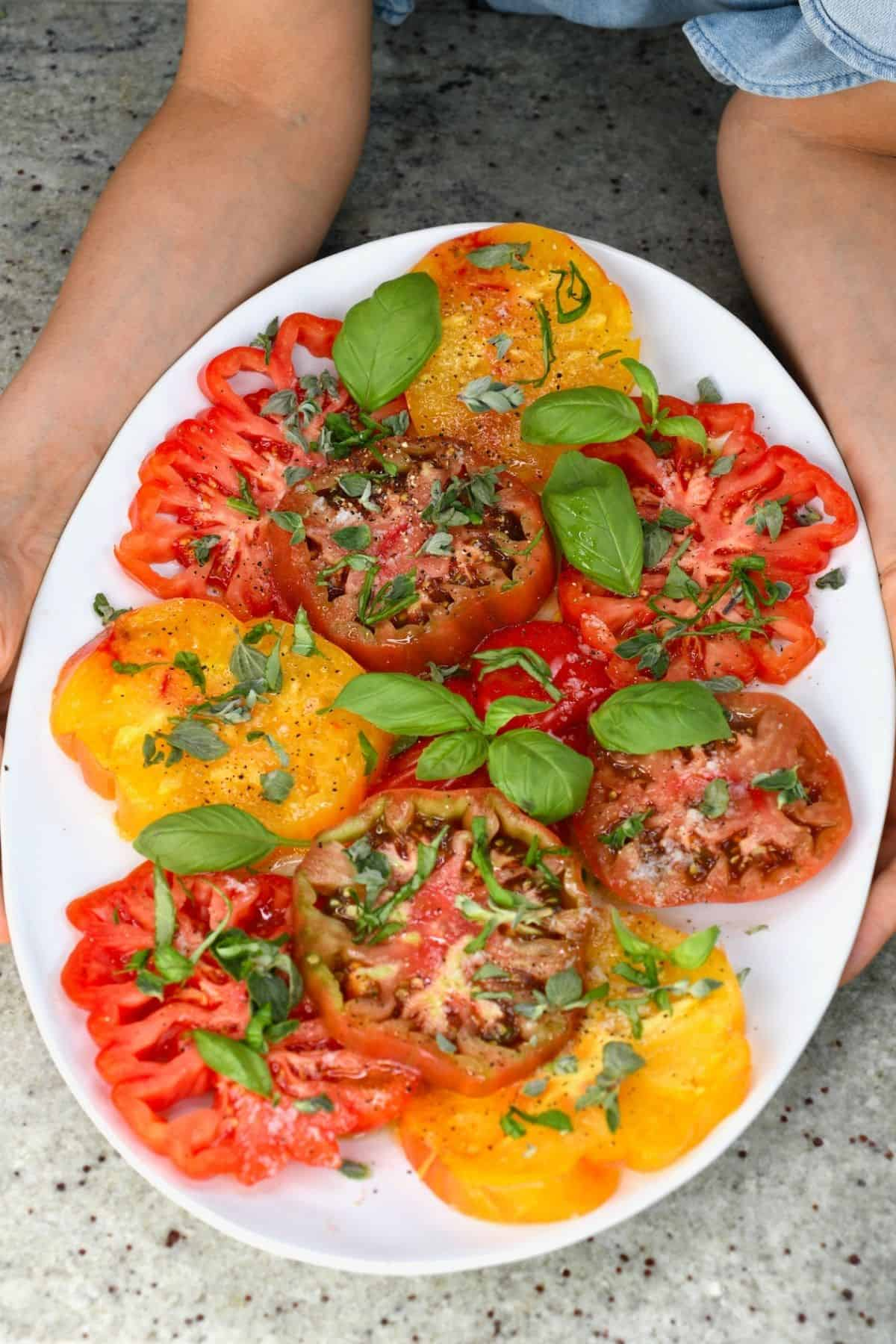Simple tomato salad topped with basil in a plate
