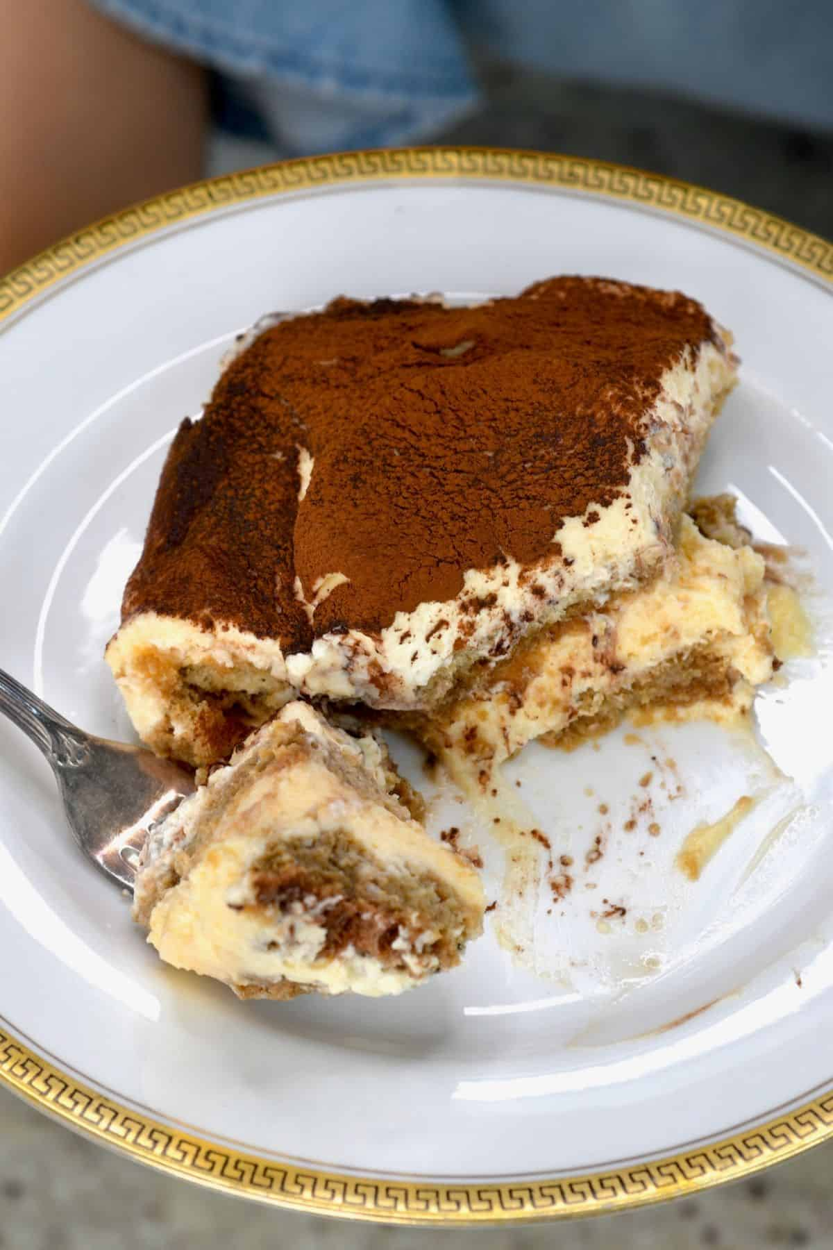 A serving of tiramisu on a plate with a fork