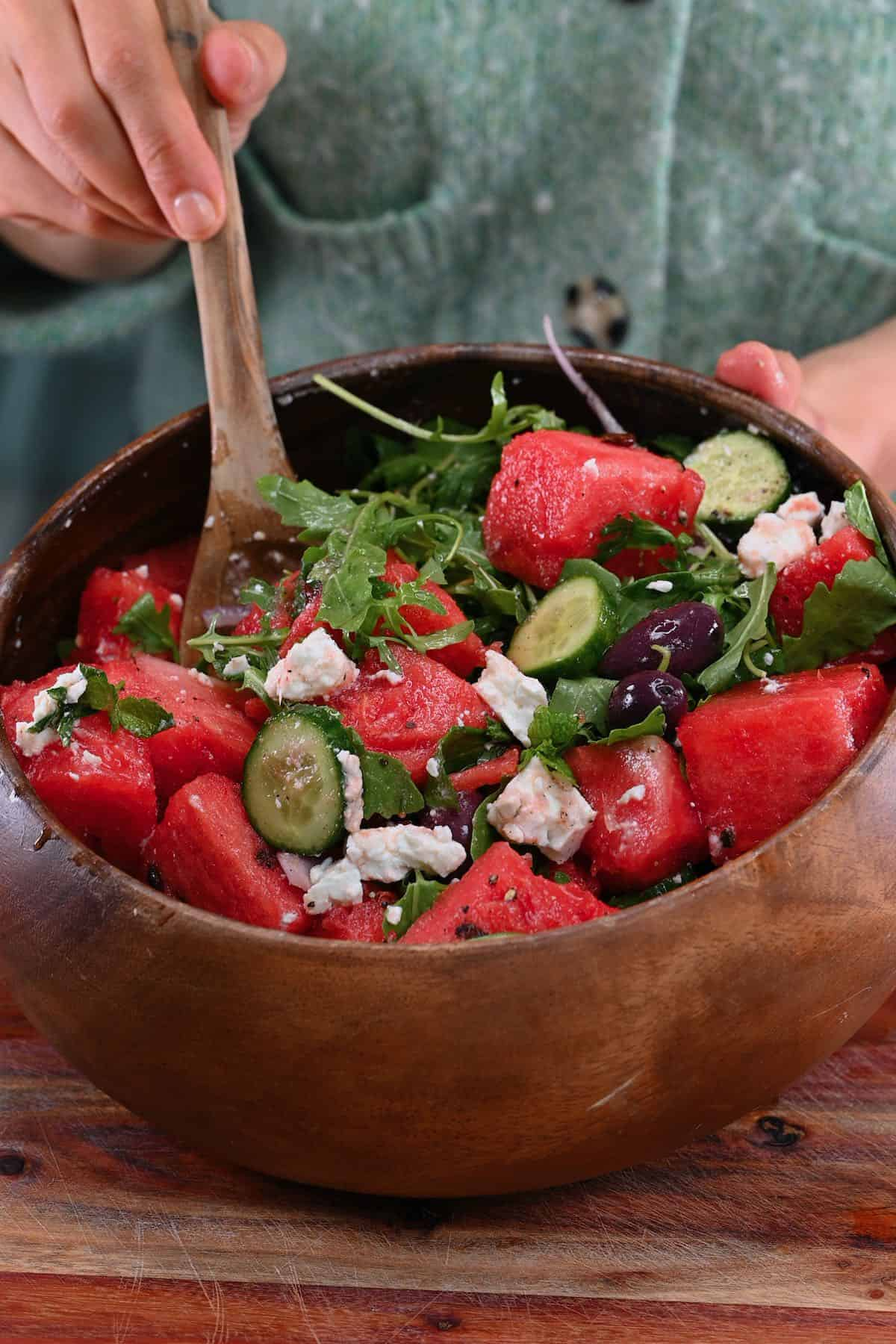 Mixing watermelon salad