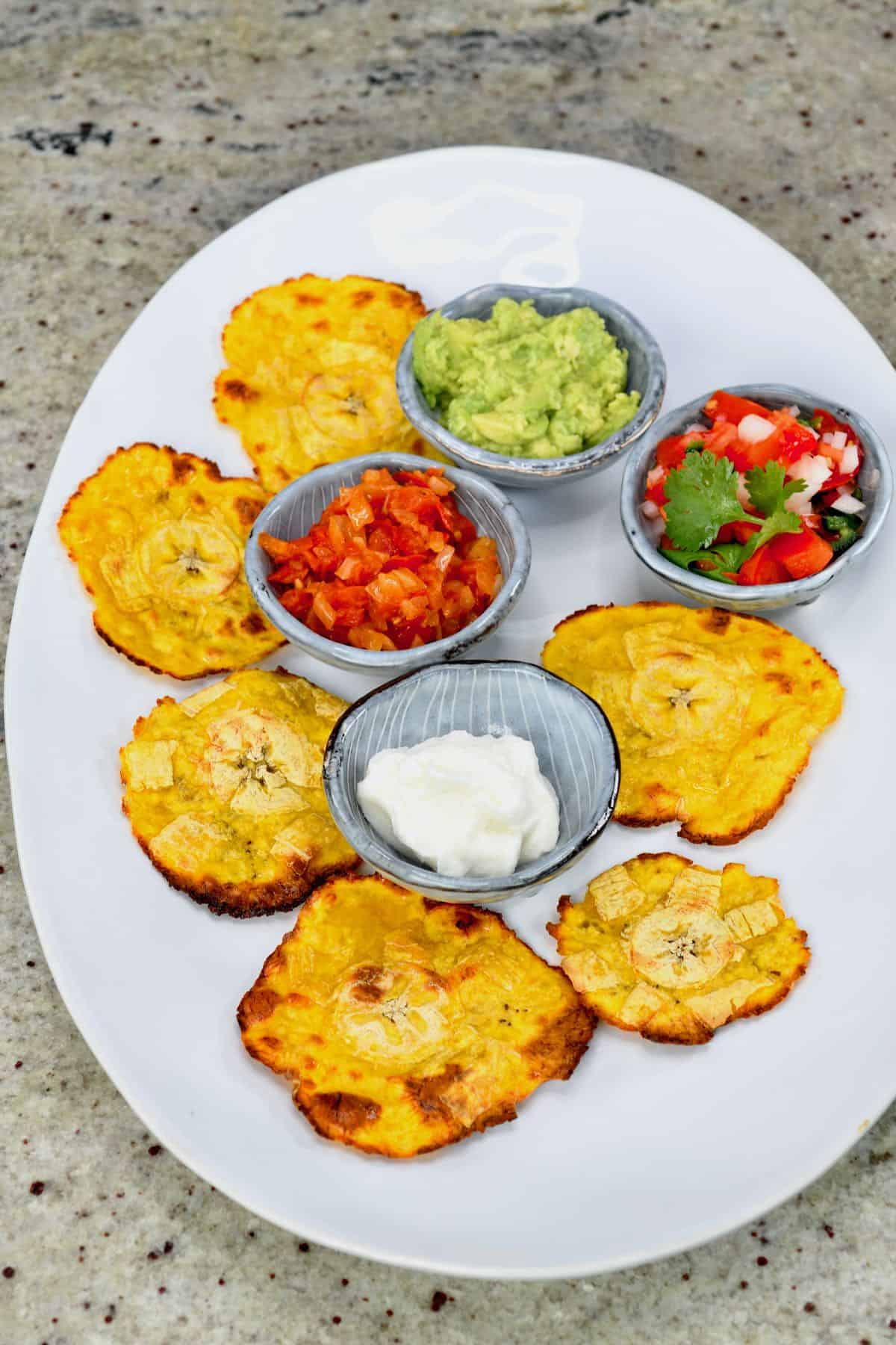 Plantain chips on a plate with salsas