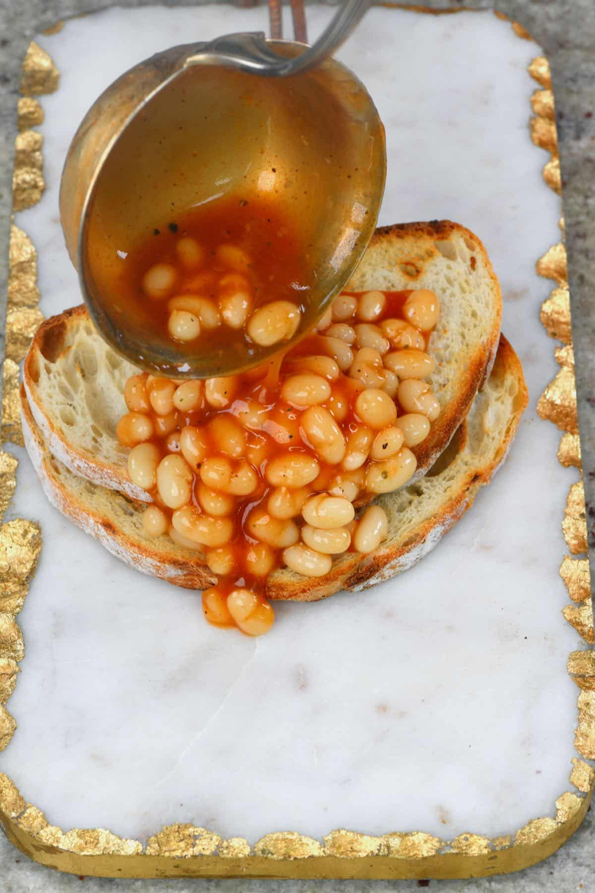 Pouring baked beans over toast