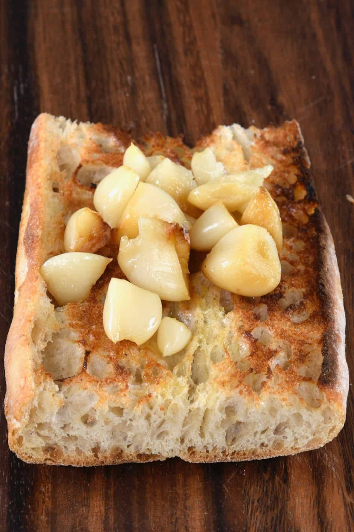 Roasted garlic cloves on top of toast