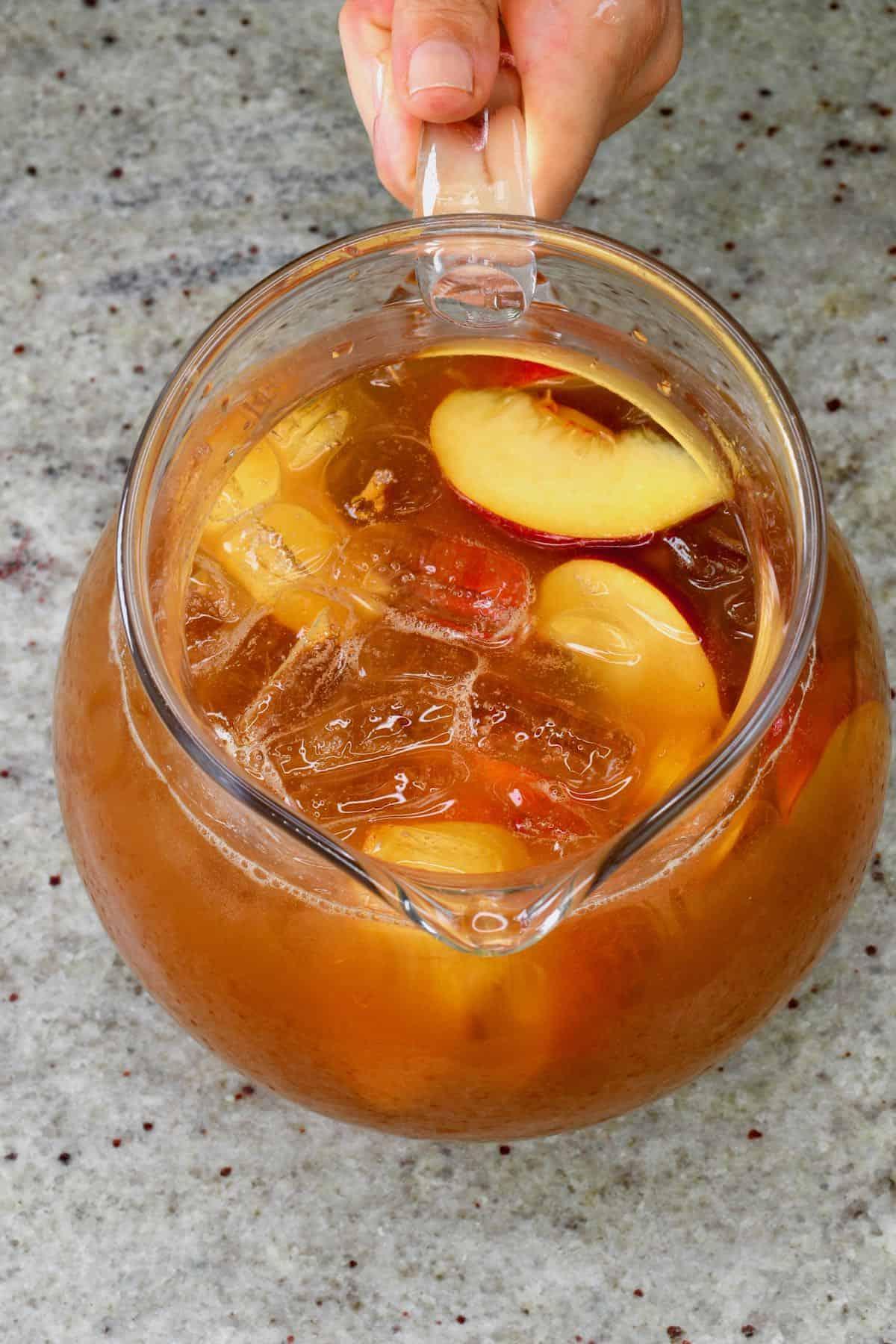 A pitcher with peach iced tea