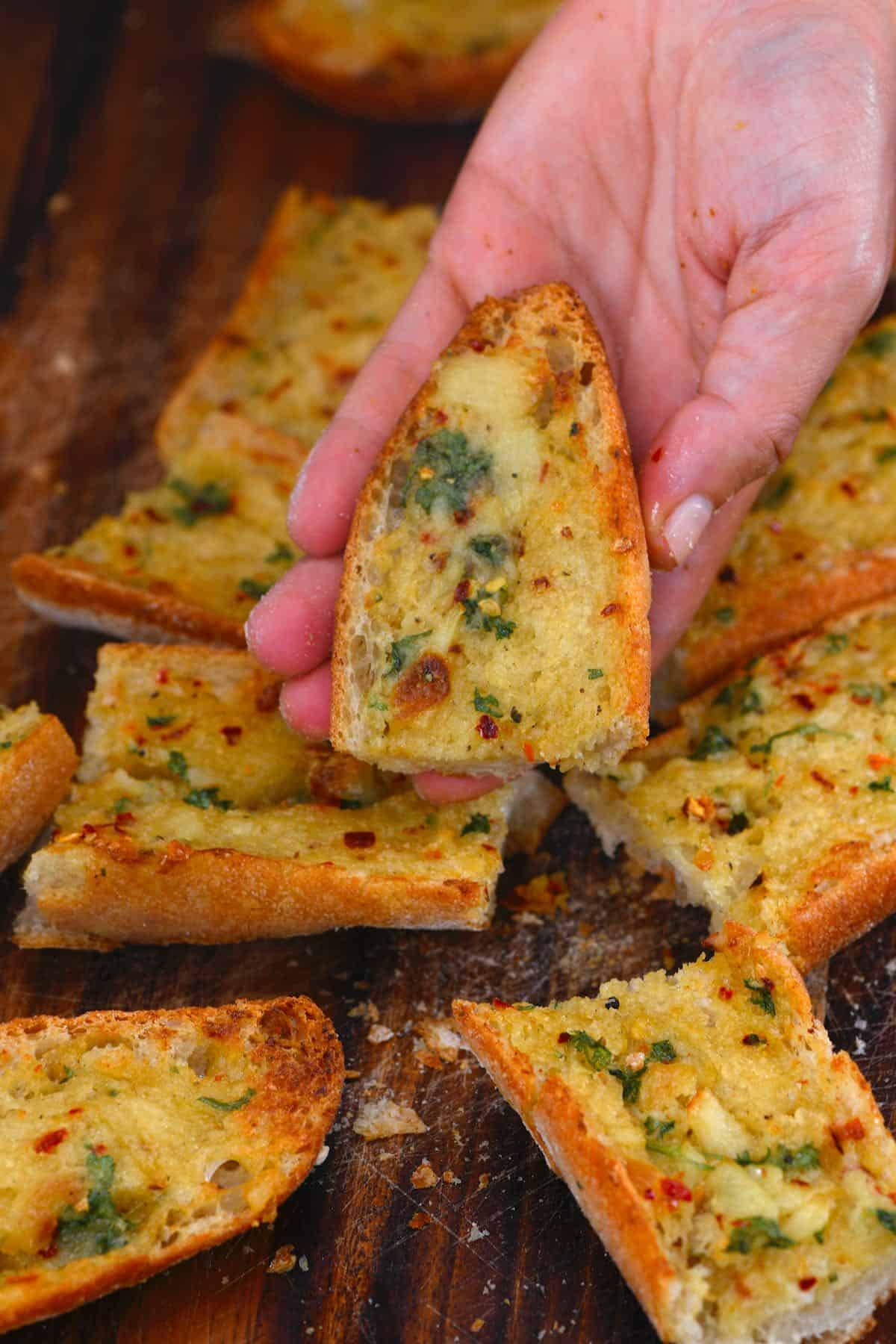 Holding a piece of roasted garlic bread
