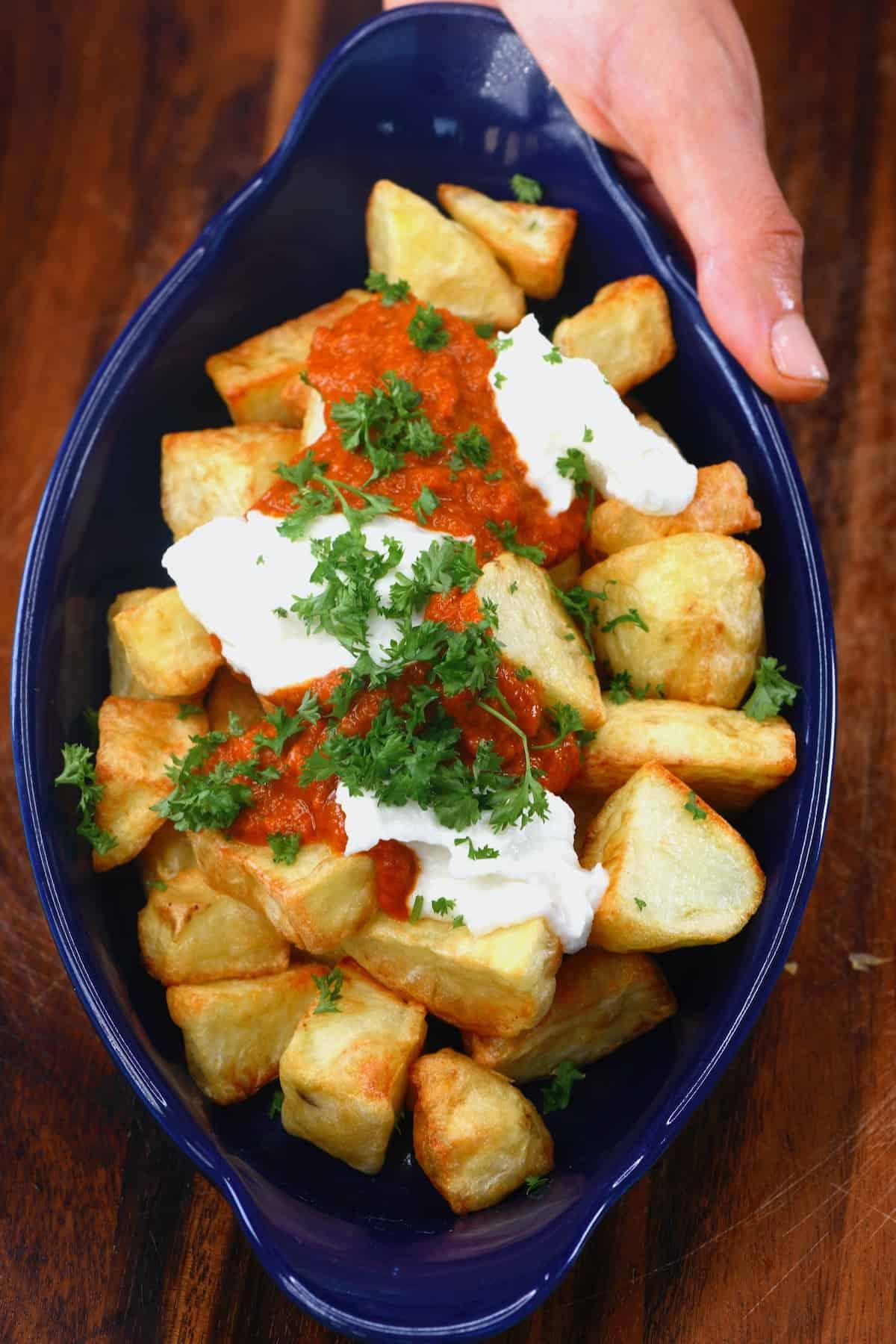 Patatas bravas topped with parsley