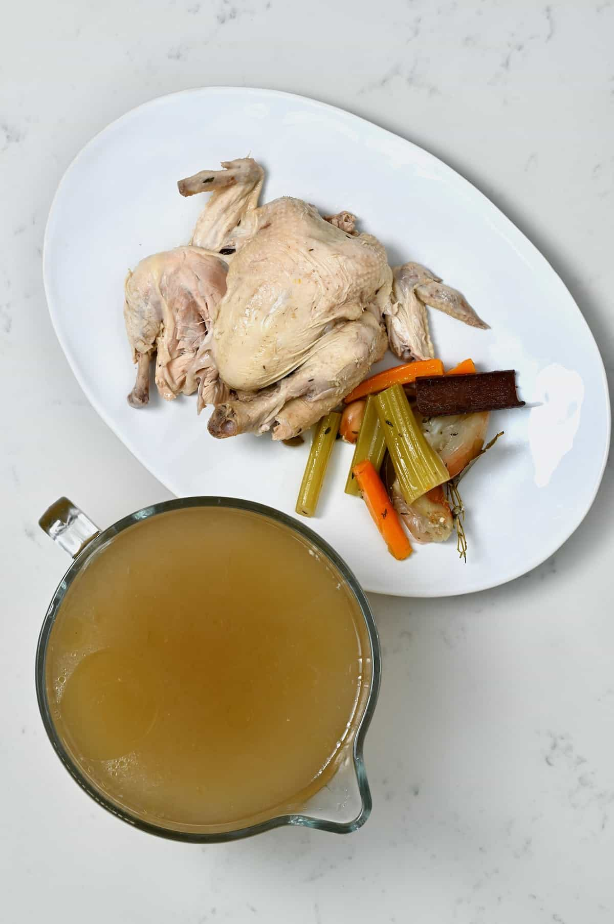 Homemade chicken stock and whole cooked chicken with vegetables