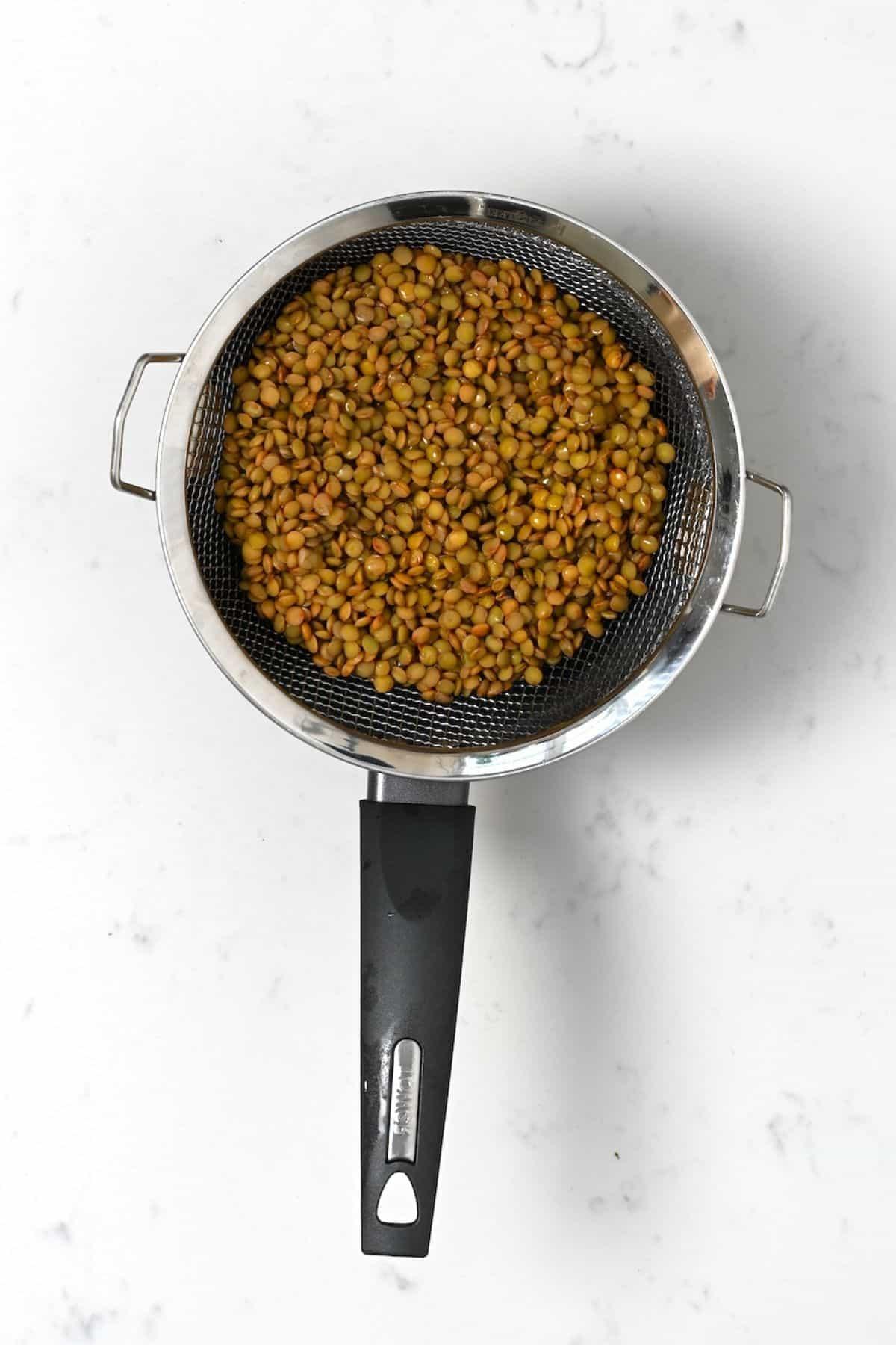 Cooked lentils in a colander