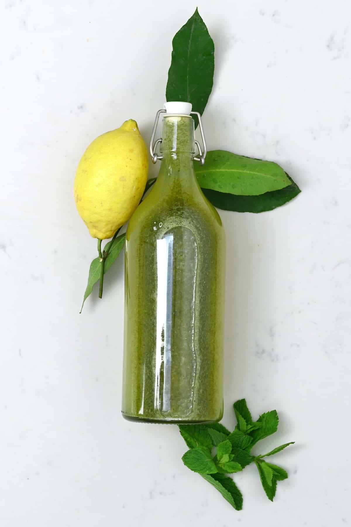 Mint lemonade in a bottle and lemon and mint leaves