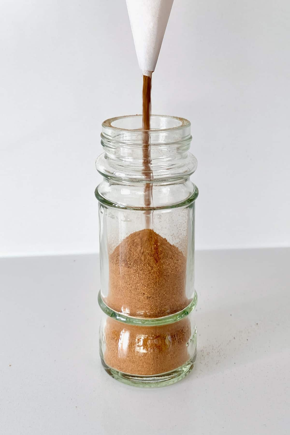 Filling a spice jar with homemade pumpkin pie spice